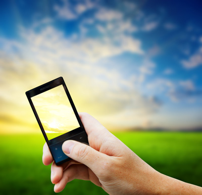 Person holding a cell phone with beautiful landscape and blue sky in the background